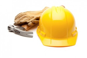 Yellow Hard Hat, Gloves and Hammer on White